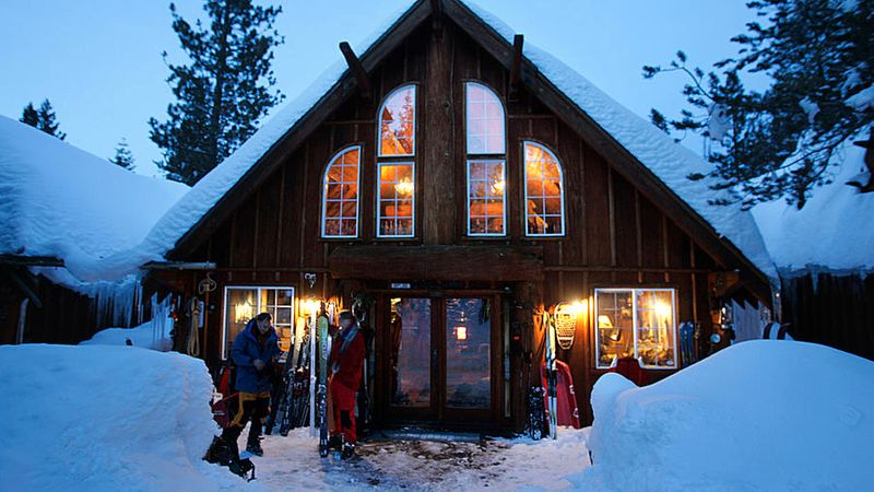 A cabin covered in snow at Lost Trail Lodge in Truckee with skiers standing outside