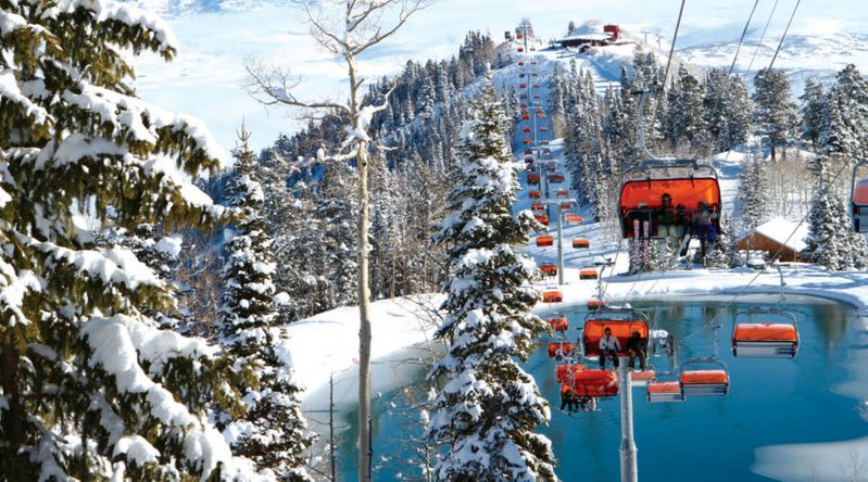 The ski gondolas at Park City Mountain surrounded by snowy slopes and trees during the day