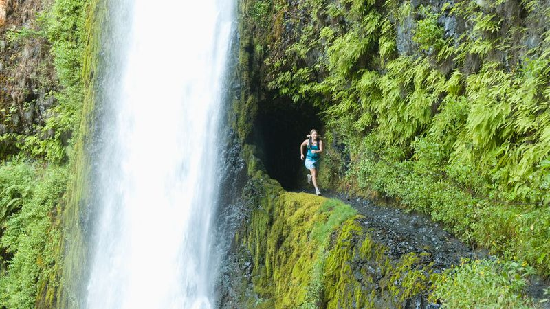 Woman running under Devils Falls on the Northern Three Sisters Wilderness area of the PCT