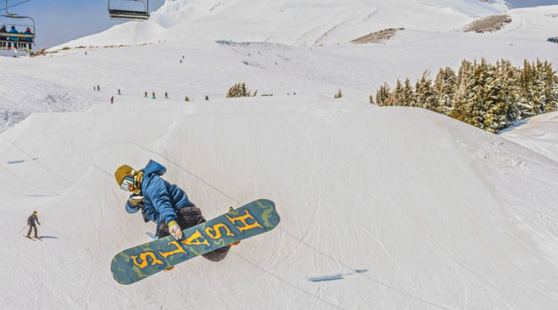 Snowboarder doing a jumping trick at Mt. Hood under the ski lift with snow and sunny skies