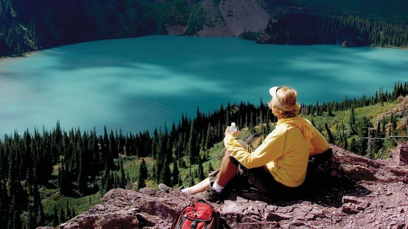Person looking at the turquoise lakes and mountains on one of the best hikes in the West, Grinnell Glacier Trail