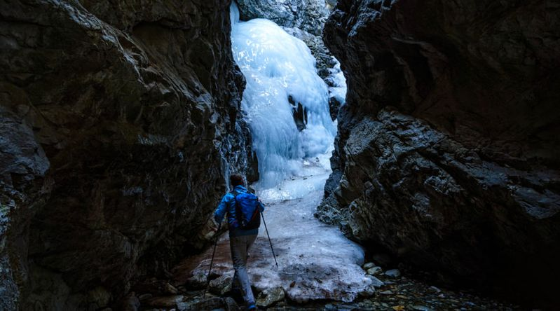 Man hiking in frozen waterfall area with water flowing Zapata Falls Canyon Waterfall in Colorado