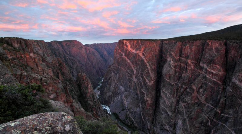 Sun rises over the Painted Wall cliff at Black Canyon of the Gunnison, Colorado, a great alternative to Grand Canyon, which is affected by overtourism