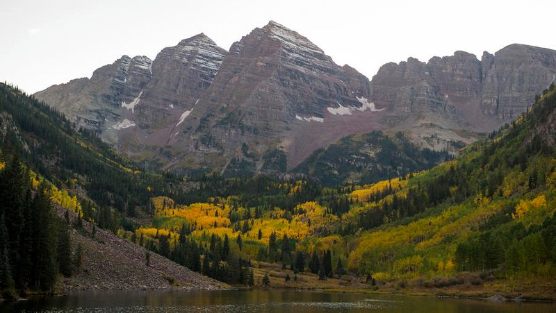 Maroon Bells, seen in front of a lake and with a snow-capped peak, one of the best fall hikes in the West