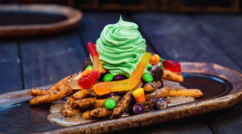 pile of funnel cake fries with green whipped topping and gummy worms