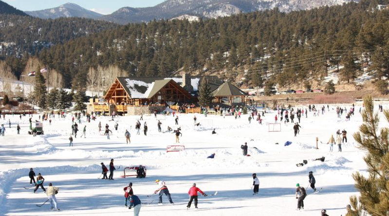 People ice skating and playing hockey on the Evergreen Lake ice skating rink with the mountains in the background