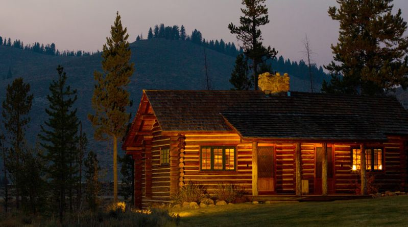 Nighttime view of cozy cabin illuminated under trees at Idaho Rocky Mountain Ranch