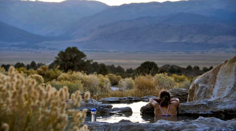 Woman soaking in a hot spring in the lower pool at Travertine Hot Springs in the California Sierra Nevada