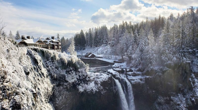 Salish Lodge surrounded by snow with the waterfall in winter