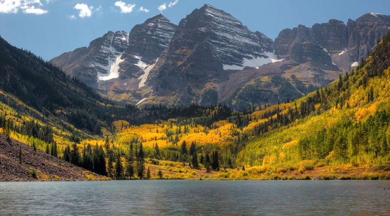 Maroon Bells, seen in front of a lake and with a snow-capped peak, is one of the best places in the country for fall color,