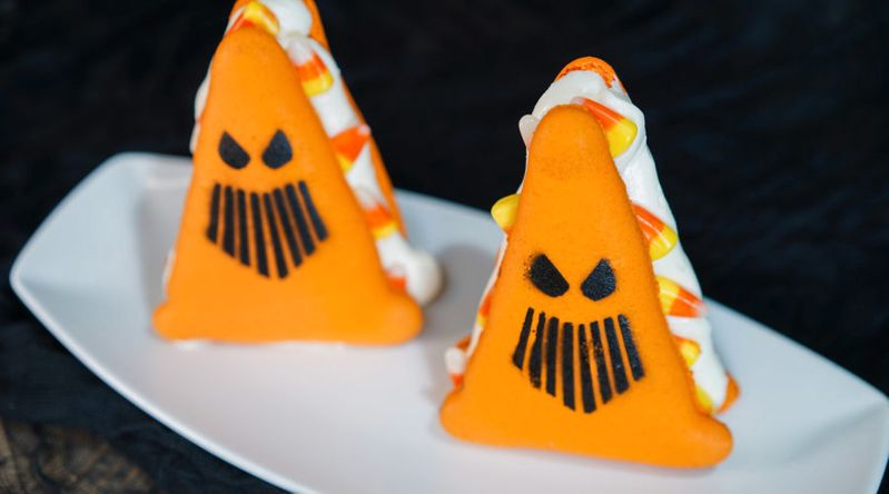 A traffic cone-shapped macaron with candy corn and buttercream filling
