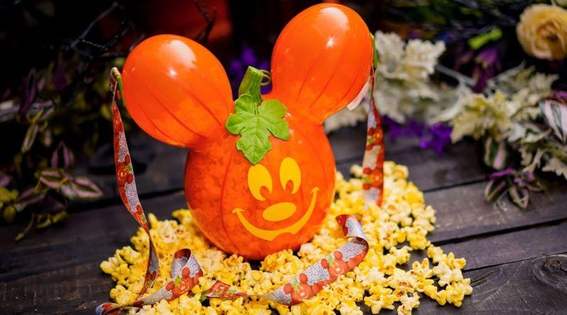 An orange popcorn bucket in the shape of mickey mouse, looks like a jack-o-lantern