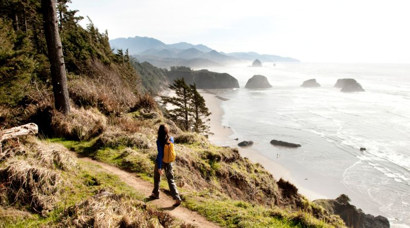 A woman hiking a path near the Oregon Coast with a Pacific Northwest trip