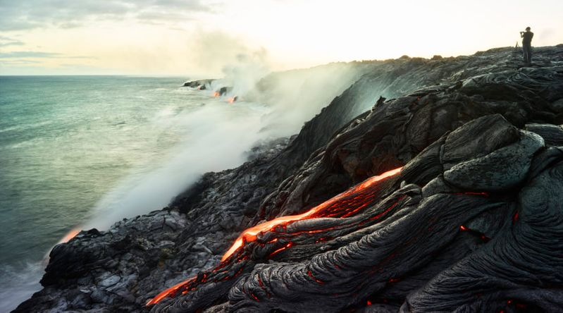 Man standing on volcano taking photo of ocean at Hawaii Volcanoes National Park, a UNESCO World Heritage Site