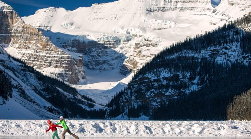 Two women skating across Lake Louis ice skating rinks with giant mountain in the background