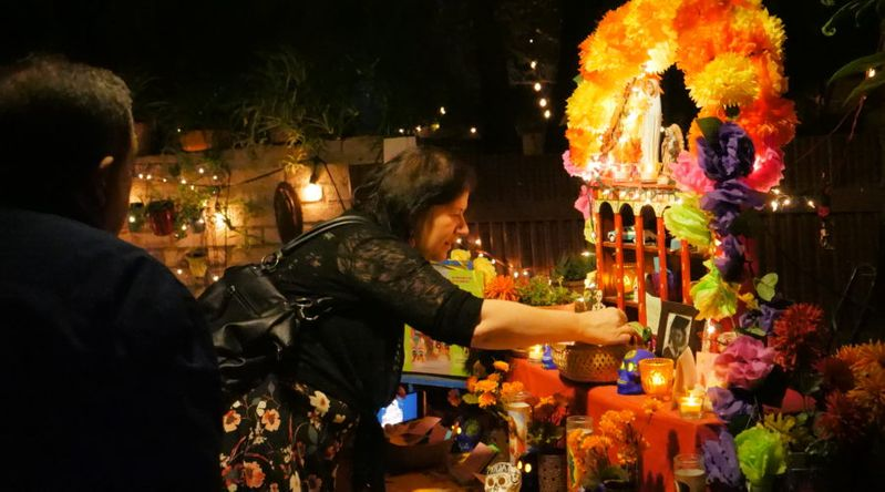 Woman placing an ofrenda (offering) on the altar during a Day of the Dead event in Tucson