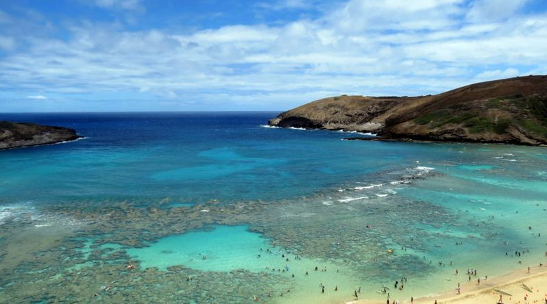 Aerial view with people of Hanauma Beach, one of the places suffering from overtourism in Hawaii.