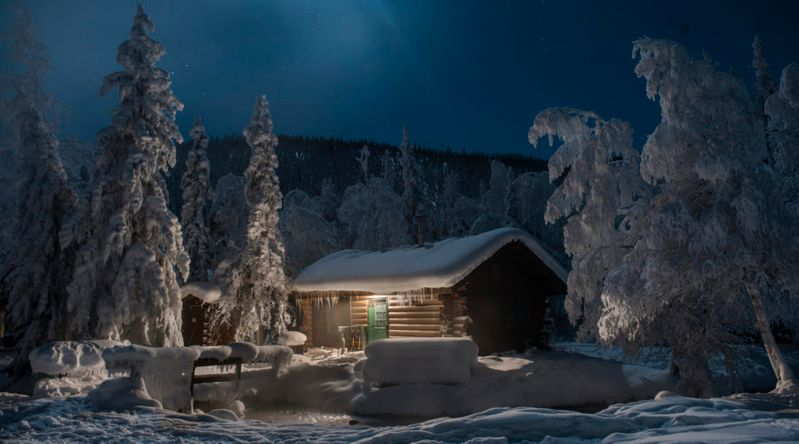 Chena Hot Springs by snow covered trees against log cabin