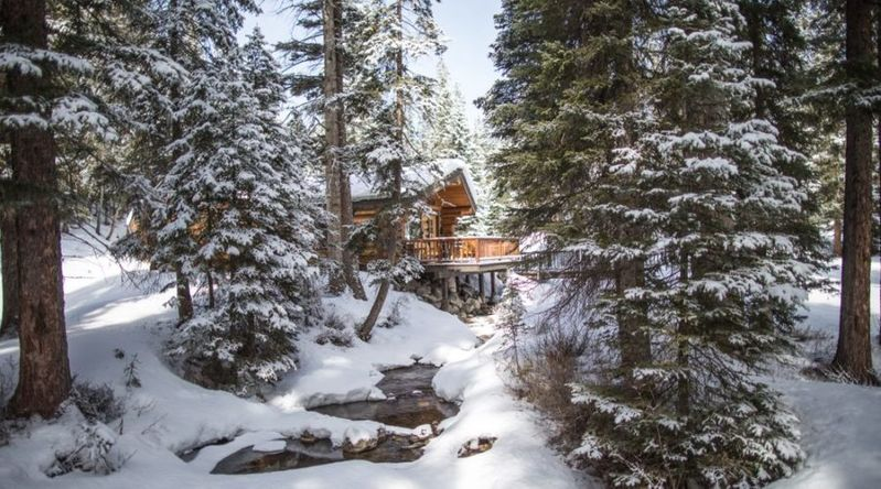 A cabin at Lone Mountain Ranch seen beyond the trees covered in snow in Montana
