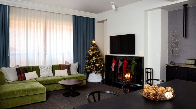 A suite inside the Kimpton Alexis Hotel decorated for the holidays with a Christmas tree and stocking around the fireplace