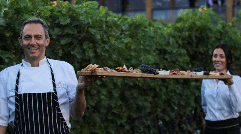Chef holding platter of meats and cheeses during a winery harvest experience in British Columbia
