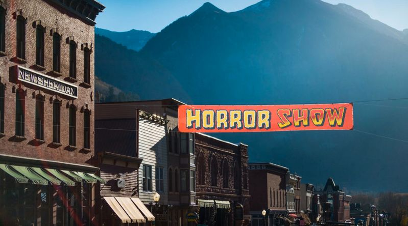 Downtown view of Telluride with a sign that advertises the town's haunted houses