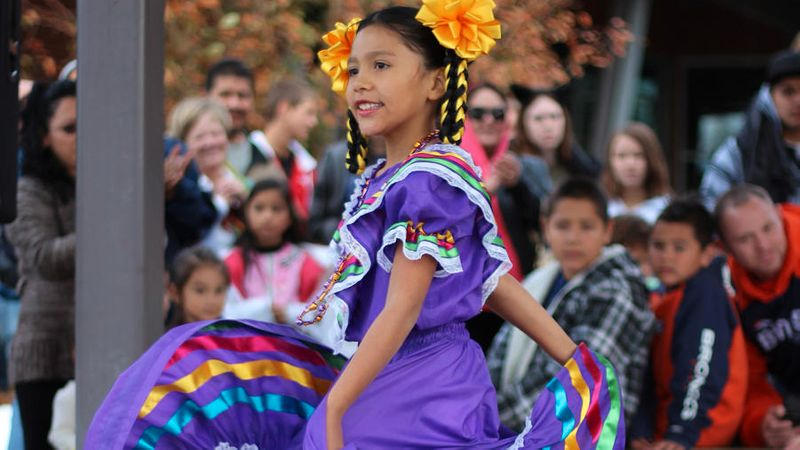 Girl in traditional Mexican purple dress at Day of the Dead event in Longmont, CO