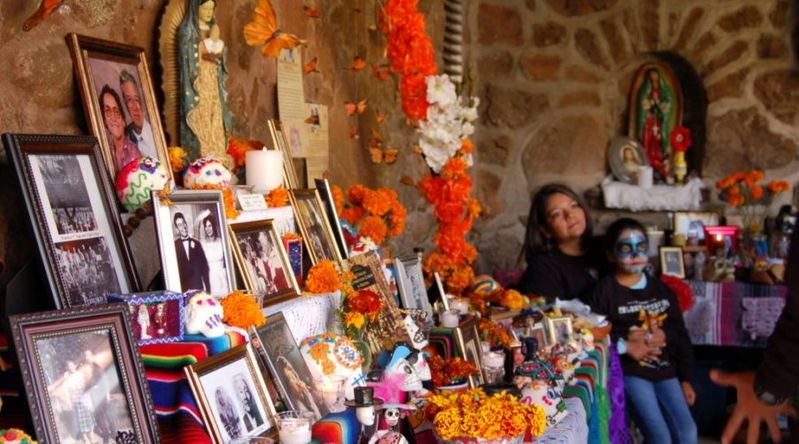 Ofrenda with mother and child in the background at a Day of the Dead event at the Museum of Northern Arizona in Flagstaff