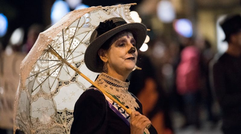 Woman in costume with Day of the Dead makeup and Victorian costume and lace umbrella