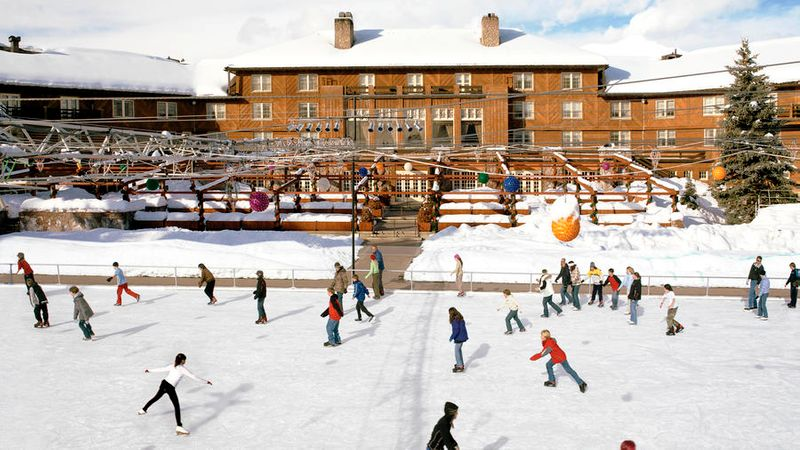 People ice skating in front of the snow-covered Sun Valley Lodge in Idaho