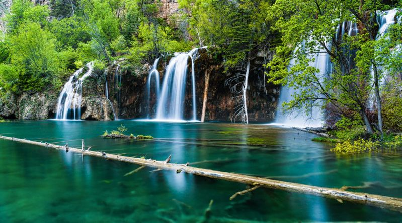 Scenic landscape of crystal clear lake and green lush foliage at Hanging Lake at Glenwood Canyon
