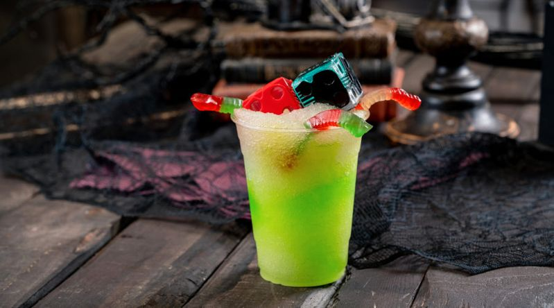 Green slushie with gummy worms and novelty oogie boogie dice